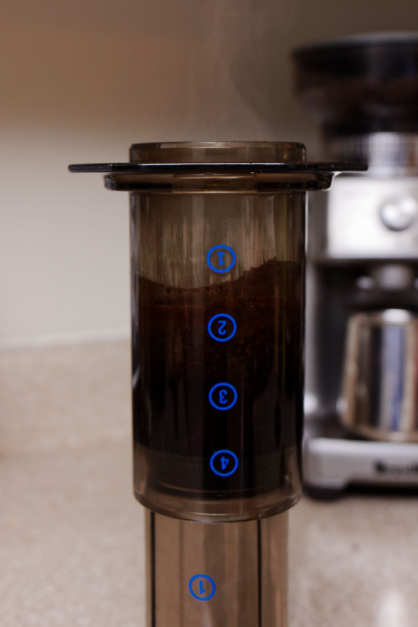 An Areopress half-filled with water and coffee grounds.