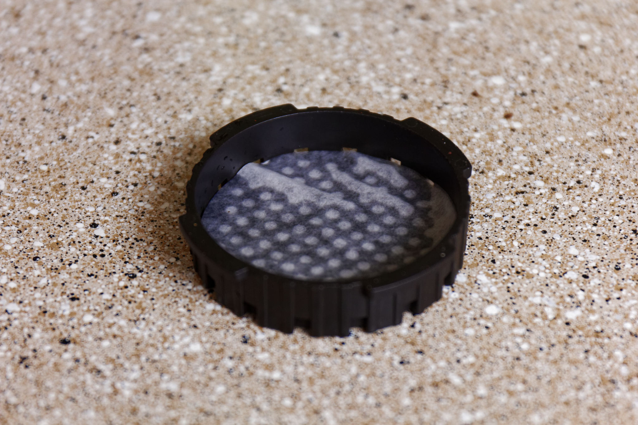 A wetted cap of an areopress with a filter.